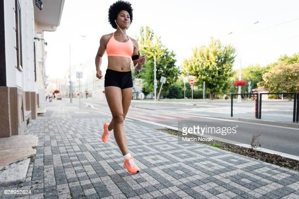 Athletic young woman jogging on sidewalk