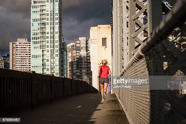 athletic young woman jogs on city bridge - forward athlete stock pictures, royalty-free photos & images