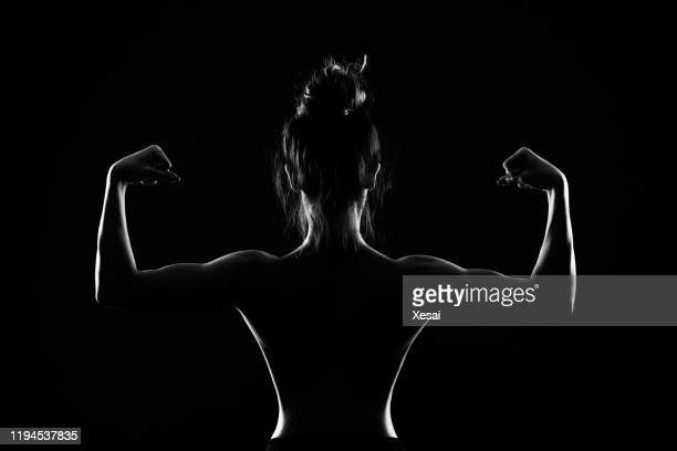 athletic young woman on black background - seductive women stock pictures, royalty-free photos & images
