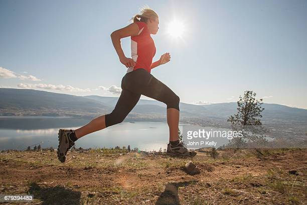 Athletic young woman running on rural trail