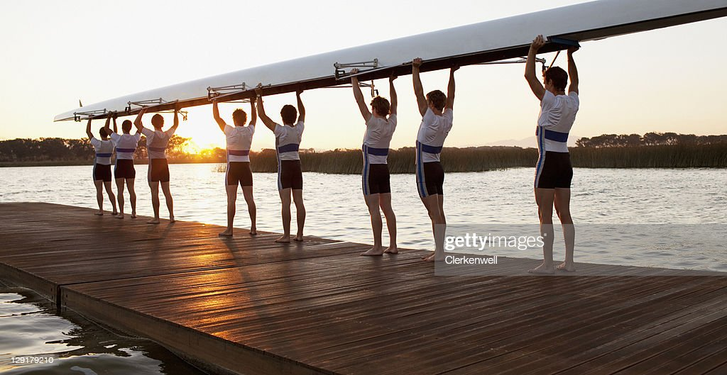 Athletics carrying a crew canoe over heads : Stock Photo