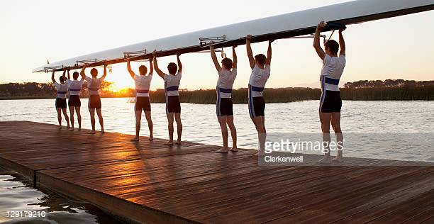 athletics carrying a crew canoe over heads - sportmannschaft stock-fotos und bilder