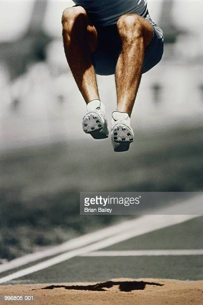 Athletics, long jump, man in mid- air jump (Digital Enhancement)