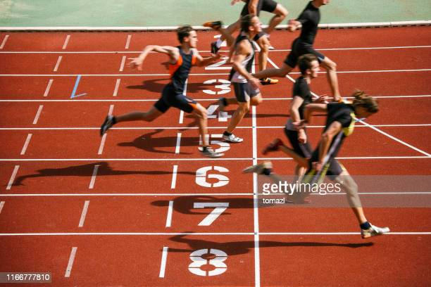 athlets sprinting at finish line - athlete stock pictures, royalty-free photos & images
