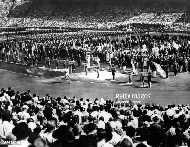 Athlète John Mark porte la flamme olympique pour un tour d'honneur du stade de Wembley lors de la cérémonie d'ouverture des Jeux Olympiques le 29...