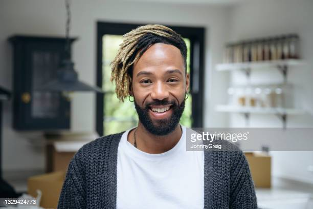 at-home portrait of relaxed black man in casual clothing - mid length hair stock pictures, royalty-free photos & images