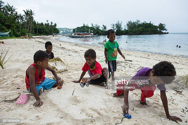ati children play on the coastline in front of their boracay ancestral domain. - public domain stock pictures, royalty-free photos & images