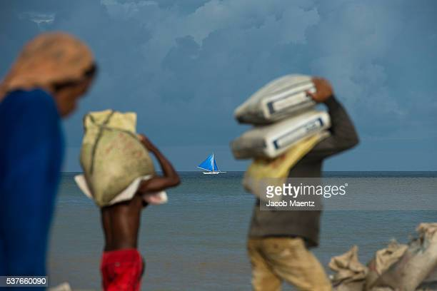 Ati men carrying goods to be shipped to Boracay