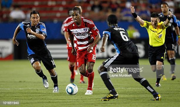 Atiba Harris of FC Dallas dribbles the ball between Arturo Alvarez and Ike Opara of the San Jose Earthquake at Pizza Hut Park on June 5 2010 in...