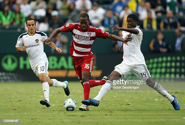 Atiba Harris of FC Dallas paces the ball between Landon Donovan and Edson Buddle of the Los Angeles Galaxy in the first half during the MLS match on...