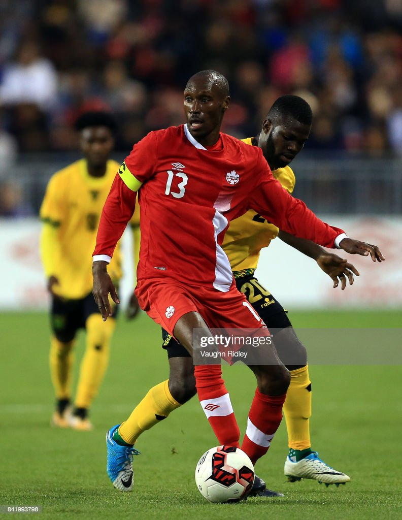 Atiba Hutchinson #13 of Canada battles for the ball with Kemar Lawrence #20 of Jamaica during the first half of an International Friendly match at BMO Field on September 2, 2017 in Toronto, Canada.
