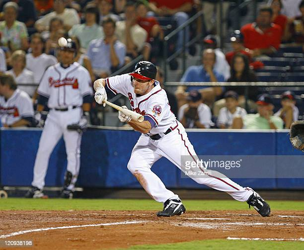 Atlanta Brave Ryan Langerhans drops a successful suicide squeeze bunt down over the pitcher's mound during the game against the San Francisco Giants...