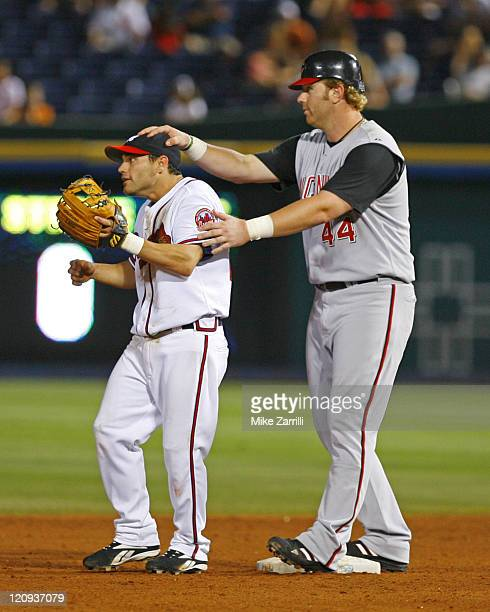 Atlanta Braves 2B Marcus Giles is distracted by Cincinnati Reds LF Adam Dunn while the cutoff throw is coming in during the game at Turner Field in...