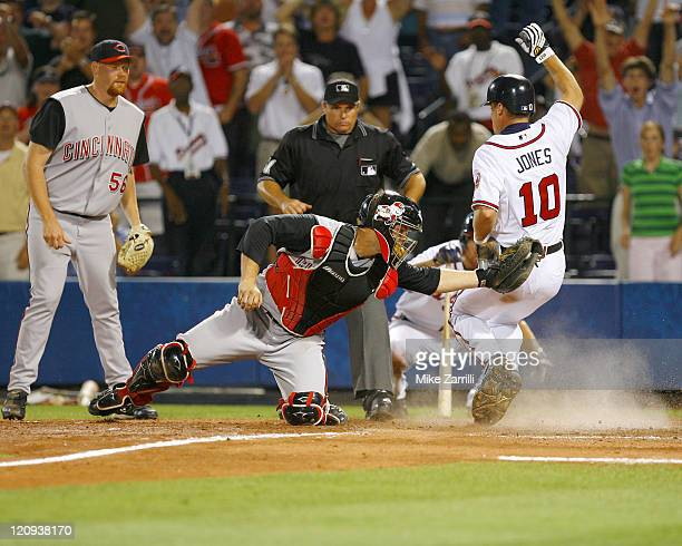 Atlanta Braves 3B Chipper Jones slides past Cincinnati Reds C David Ross for the winning run in the bottom of the 10th inning during the game at...