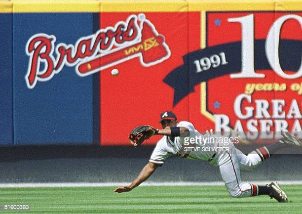 Atlanta Braves' Andruw Jones dives for a ninth inning line drive hit by Florida Marlins' Cliff Floyd 18 April 2001 at Turner Field in Atlanta Georgia...