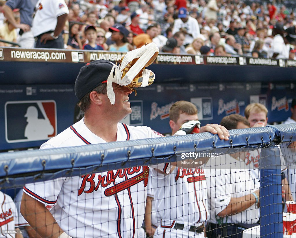 Atlanta Braves C Todd Pratt tapes a glove to his head as a practical joke against Florida Marlins 1B Michael Jacobs, who let an errant warmup throw go into the dugout and hit Pratt in the head during the previous night's game, during the game between the Florida Marlins and the Atlanta Braves on July 26, 2006 at Turner Field in Atlanta, GA. The Braves beat the Marlins 6-5.