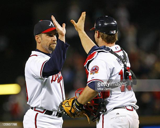Atlanta Braves pitcher John Smoltz is congratulated by catcher Brian McCann after Smoltz's complete game win against the Washington Nationals at...