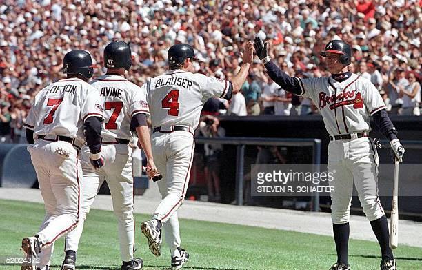 Atlanta Braves player Chipper Jones greets teammates Kenny Lofton Tom Glavine and Jeff Blauser after Blauser hit a threerun home run in the third...