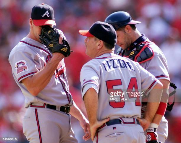 Atlanta Braves relief pitcher John Rocker wipes his face during a visit to the mound by coach Leo Mazzone and catcher Paul Bako during the eighth...