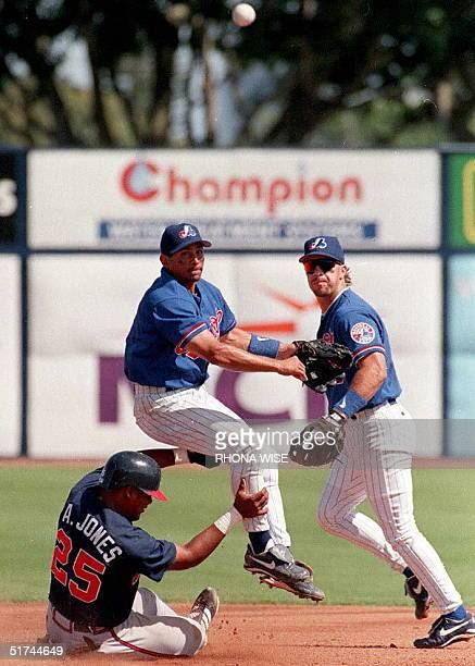 Atlanta Braves rightfielder Andruw Jones tries to stop Montreal Expos' shortstop Andy Stankiewicz from landing on him as he completes the double play...