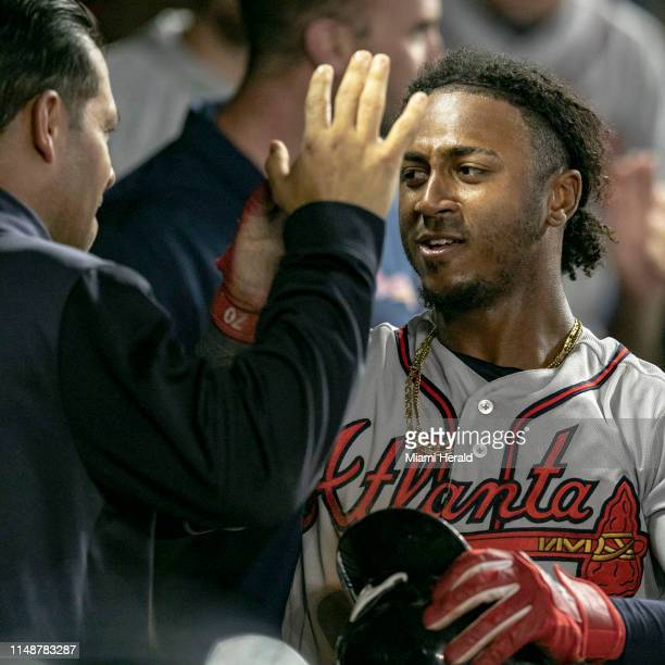 Atlanta Braves second baseman Ozzie Albies celebrates with his teammates in the dugout after scoring a run off a walk by utility player Charlie...