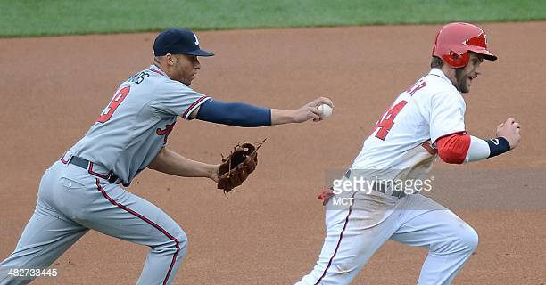 Atlanta Braves shortstop Andrelton Simmons prepares to tag out Washington Nationals left fielder Bryce Harper during a rundown between first base and...