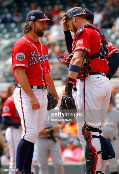 Atlanta Braves starting pitcher RA Dickey meets with Atlanta Braves catcher Tyler Flowers during the major league baseball game between the Atlanta...