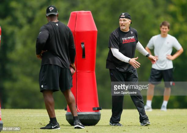 Atlanta Falcons head coach Dan Quinn demonstrates a drill during a football practice in Flowery Branch Ga