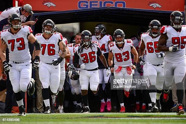 Atlanta Falcons players, including Kemal Ishmael and Jacob Tamme, run onto the field before a game against the Denver Broncos at Sports Authority...
