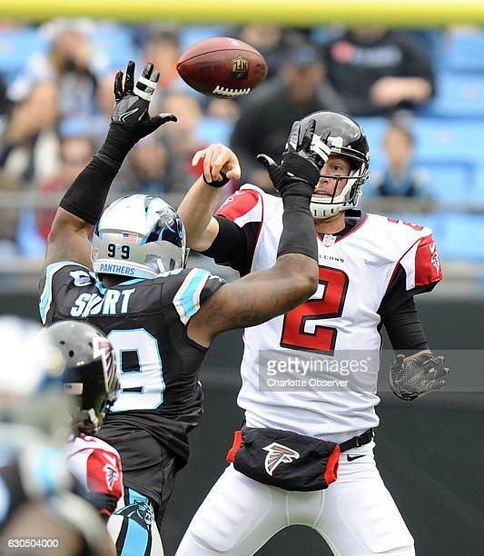 Atlanta Falcons quarterback Matt Ryan makes a pass over the arm of Carolina Panthers defensive tackle Kawann Short in the first half on Saturday Dec...