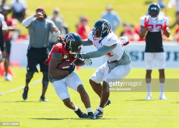 Atlanta Falcons running back Devonta Freeman and cornerback Brian Poole take part of a drill on August 01 2017 during the Atlanta Falcons Training...