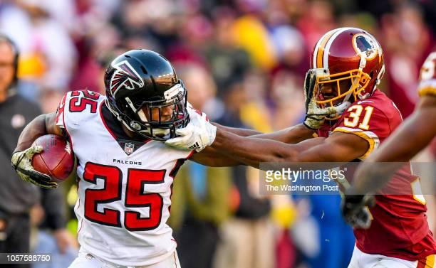 Atlanta Falcons running back Ito Smith stiff arms Washington Redskins cornerback Fabian Moreau on a fourth quarter run at FedEx Field