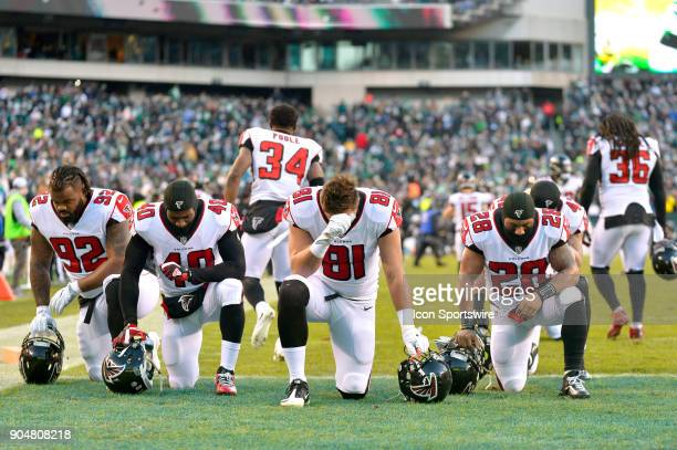 Atlanta Falcons tight end Austin Hooper and some of the Atlanta Falcons kneel in the endzone before the NFC divisional playoff game between the...