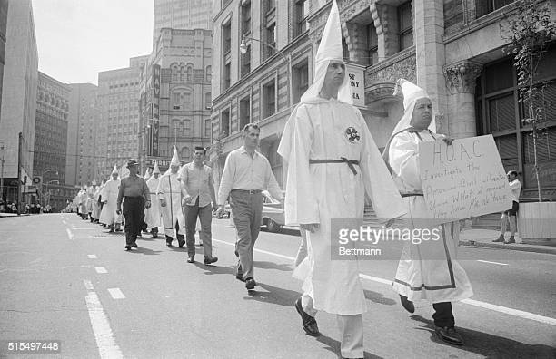 A long line of KKK members and others trod down one of Atlanta's streets here The Klansmen carried flags and signs this sign called for the House...