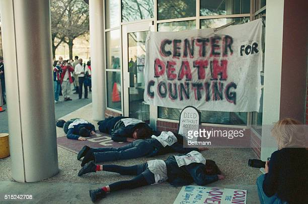 Gay rights activists play dead at the main entrance to the Centers for Disease Control after renaming it with a banner as the Center for Death...