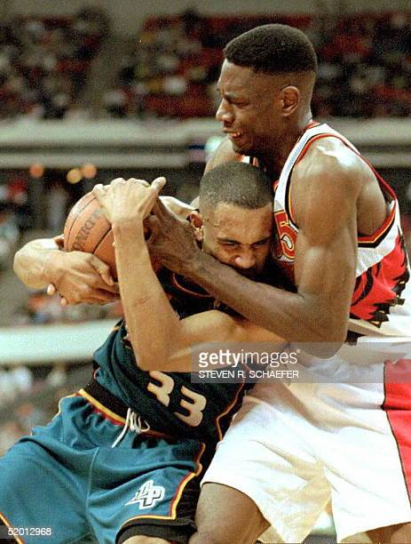 Atlanta Hawks center Dikembe Mutombo and Detroit Pistons Grant Hill struggle for the ball during the first game of the first round of the NBA...