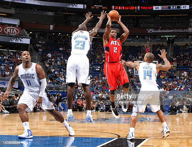 Atlanta Hawks forward Joe Johnson passes over Orlando Magic guards Jason Richardson and Jameer Nelson during the third quarter at Amway Arena in...