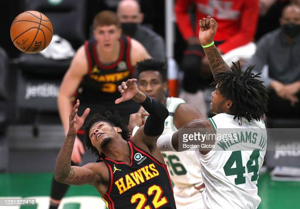 Atlanta Hawks guard Cam Reddish , left, battles for a rebound under the Hawks basket with Boston Celtics center Robert Williams III in the second...