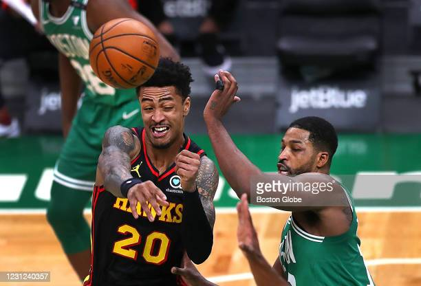 Atlanta Hawks' John Collins fires a pass in the first quarter as Boston Celtics Tristan Thompson defends under the Hawks basket. The Boston Celtics...