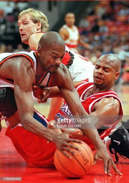 Atlanta Hawks' Stacey Augman dives past Philadelphia 76ers' Richard Dumas for a loose ball as Hawks Craig Ehlo looks on 29 November in Atlanta,...