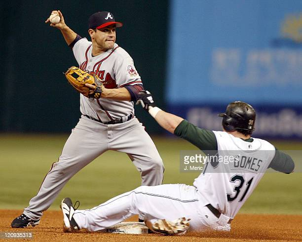 Atlanta second baseman Marcus Giles turns the double play as Tampa Bay's Jonny Gomes tries to break it up in Friday night's action at Tropicana Field...