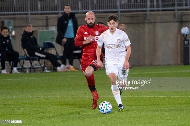 Atlanta United FC Midfielder Emerson Hyndman dribbles the ball up the field with Toronto FC Defender Laurent Ciman in pursuit during the first half...