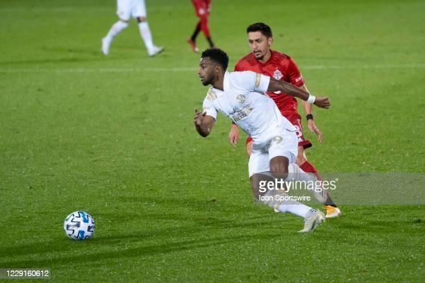 Atlanta United FC Midfielder Mo Adams ] dribbles the ball with Toronto FC Midfielder Mark Delgado in pursuit during the second half of a Major League...