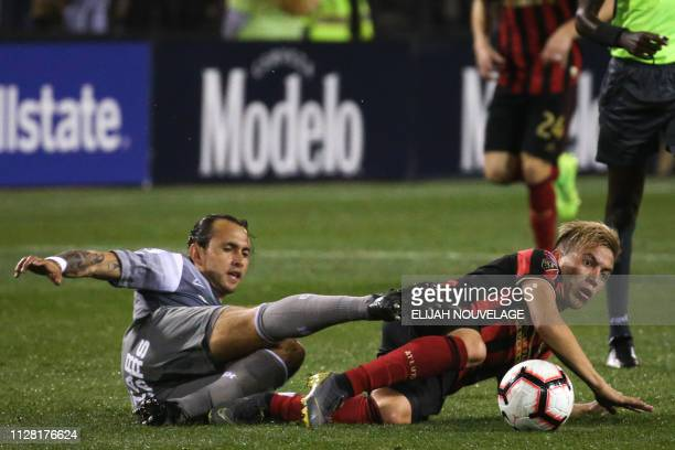 Atlanta United midfielder Ezequiel Barco and a Herediano player scramble to get to the ball after falling in the first half of the CONCACAF Champions...