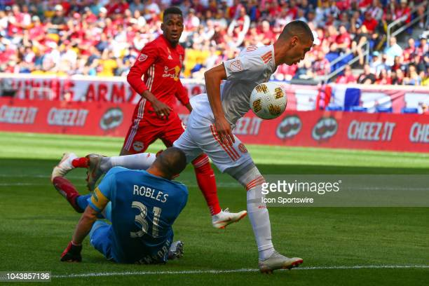Atlanta United midfielder Miguel Almiron runs into New York Red Bulls goalkeeper Luis Robles during the first half of the Major League Soccer game...