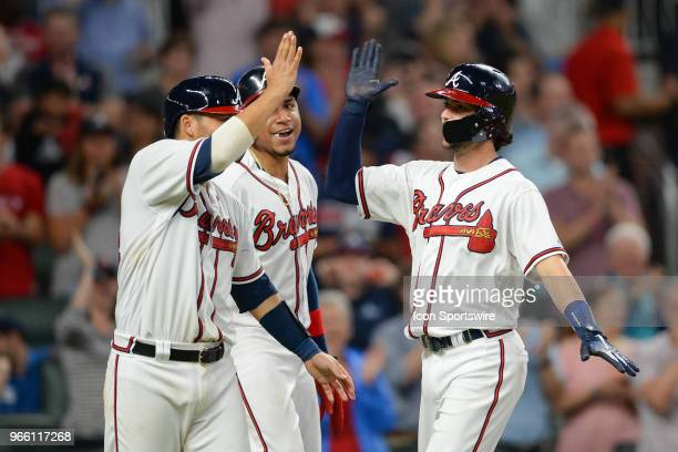 Atlanta's Dansby Swanson is congratulated by catcher Kurt Suzuki and Johan Camargo after hitting a home run during the game between Atlanta and...