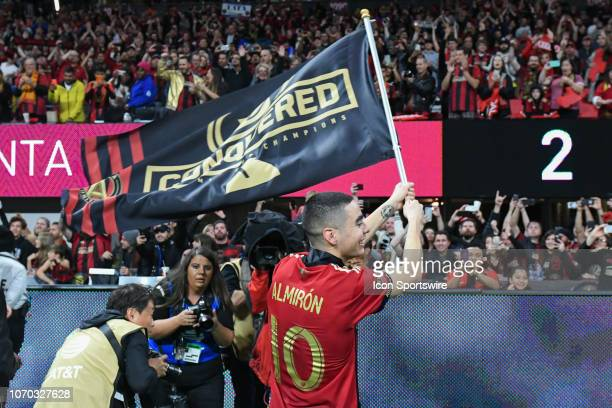 Atlanta's Miguel Almiron waves a flag at the fans in the postgame celebration during the MLS Cup between the Portland Timbers and Atlanta United FC...