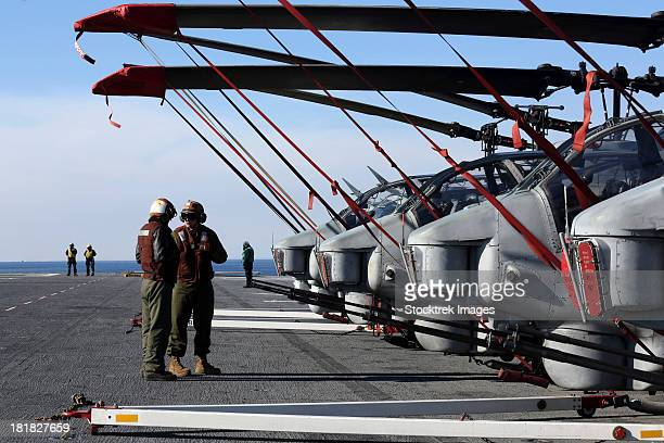 Atlantic Ocean, January 23, 2013 - Marines stand next to a row of AH-1N Cobra helicopters on the flight deck of the amphibious assault ship USS Kearsarge