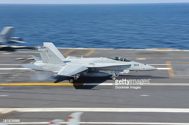atlantic ocean, january 25, 2012 - an f/a-18c hornet lands aboard the aircraft carrier uss george h.w. bush during carrier qualifications.  - landing gear stock photos and pictures