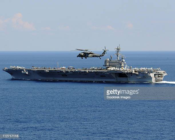 Atlantic Ocean, October 10, 2010 - An MH-60S Seahawk helicopter flies over the aircraft carrier USS George H.W. Bush (CVN-77).